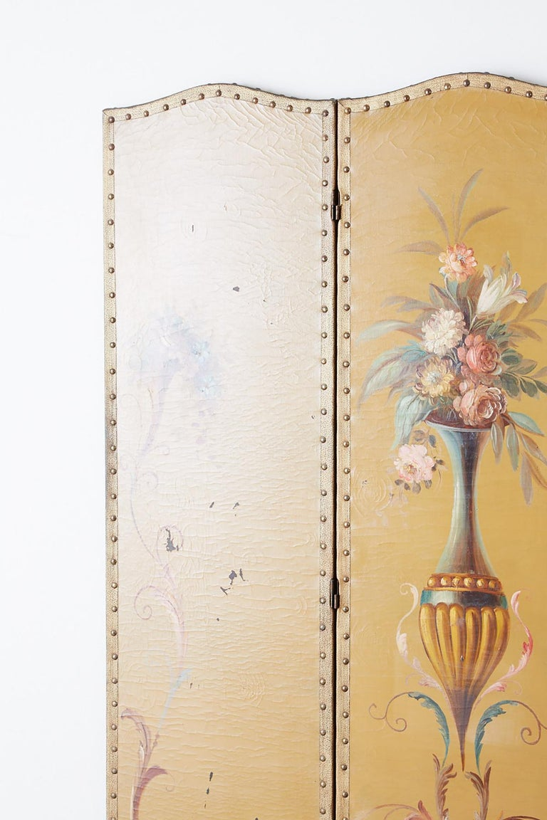 Enchanting English Victorian era three-panel painted folding floor screen. Made in the Adams style featuring a large Roman vase decorated with colorful flowers and arabesque vine scrolls. The dressing screen has a wooden frame covered with canvas