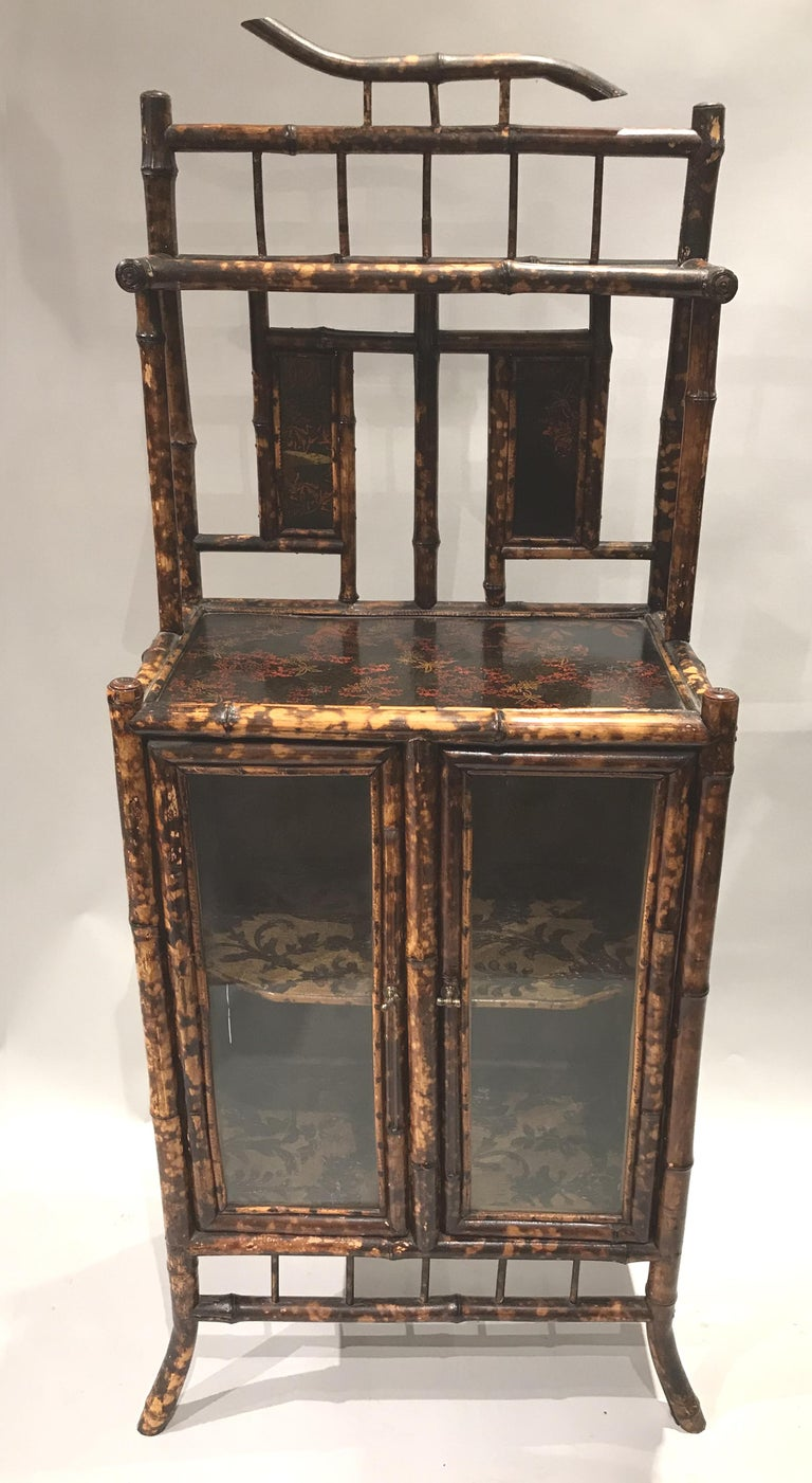 A fine English Victorian bamboo cabinet or etagere with foliate decorated shelves and two glass doors which open to a foliate paper lined one shelf interior compartment. Very good condition, with minor losses and restorations, as well as light