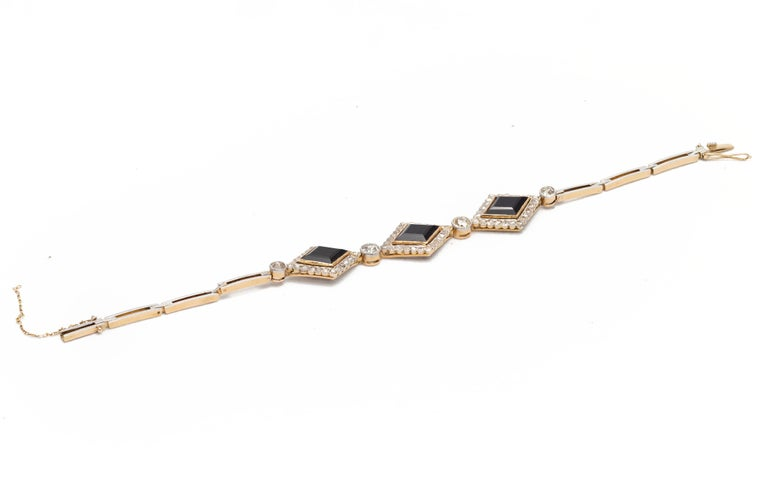 An English Victorian period Onyx and Diamond bracelet in 18K gold from the late 19th century, with lozenge motifs. With an approximate total weight of 2 carats, this Victorian bracelet features three lozenge-shaped onyx, surrounded by small rose cut