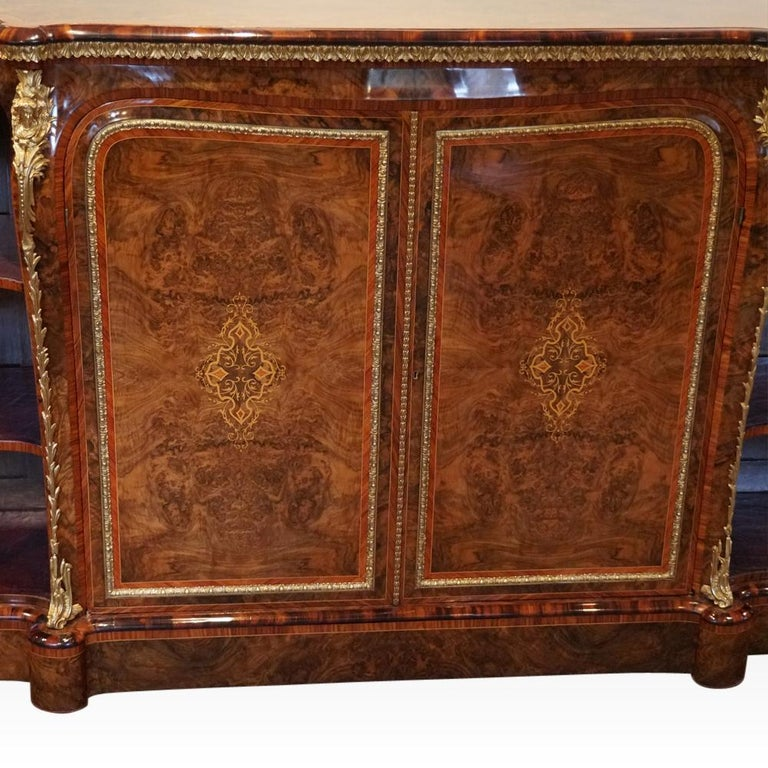 Victorian inlaid walnut side cabinet This Victorian inlaid walnut side cabinet was made circa 1870 in one of the finest workshops of the period. To each side of the pair of cupboard doors are display shelves lined in tooled leather. The cupboard
