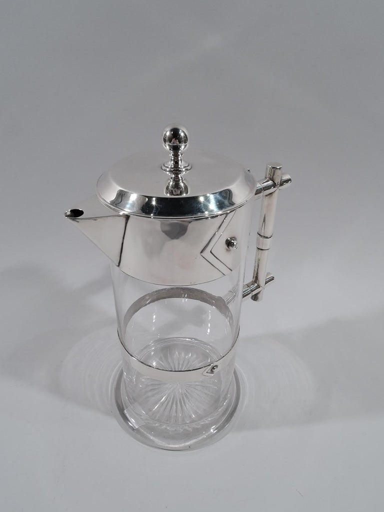 Victorian modern sterling silver and glass decanter. Made by Edgar Finley & Hugh Taylor in Birmingham in 1884. Clear glass cylinder on round and spread base. Flat girdle with applied chevron and stud. Rim collar same with triangular spout. Cover
