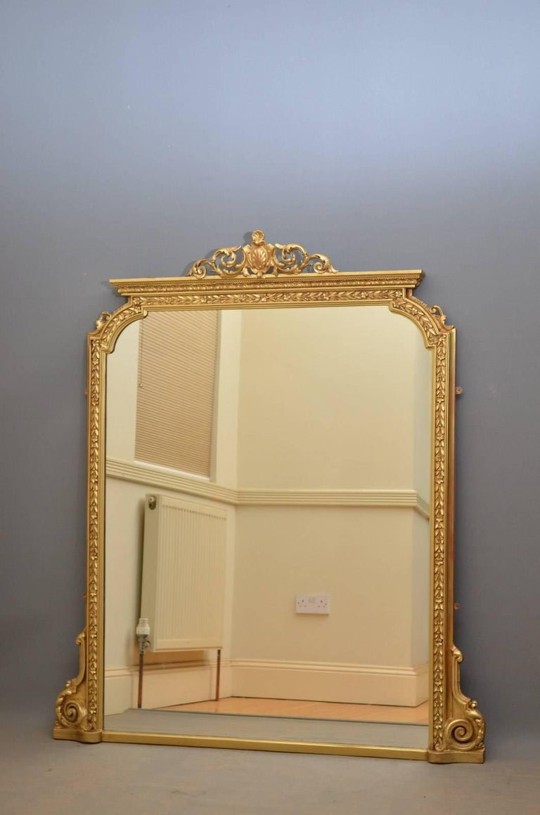 K0338 Large Victorian gilt wall mirror, having scroll cartouche to centre and original mirror plate with some foxing in finely decorated frame all flanked by foliage scrolls to base. This antique mirror has been refinished and is in home ready