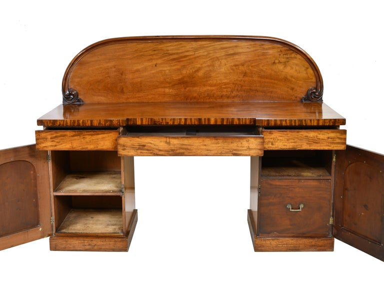 Light figured mahogany pedestal base sideboard with backsplash and ample storage from the mid to late Victorian period in England. Inside storage includes a shelf in the left cabinet and a large bottle drawer on the right as well as 3 silverware