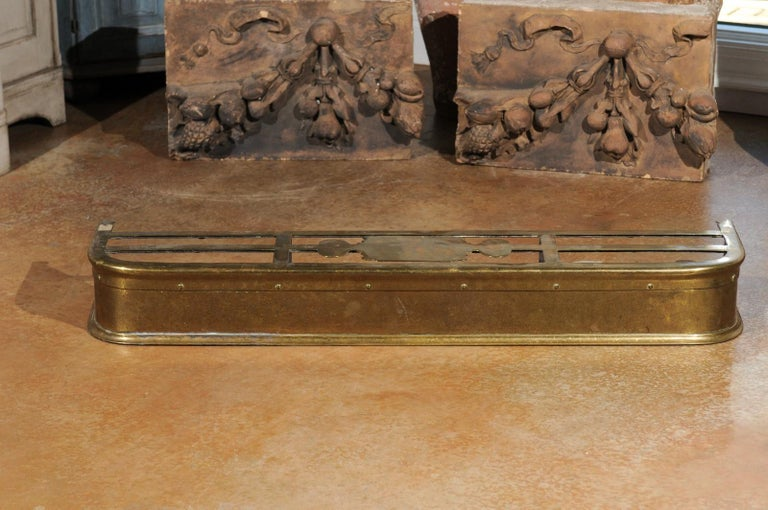 An English Victorian period brass fireplace fender from the late 19th century. Born under the reign of Queen Victoria in the later decades of the 19th century, this brass hearth fender was created to prevent logs from rolling out on the floor.