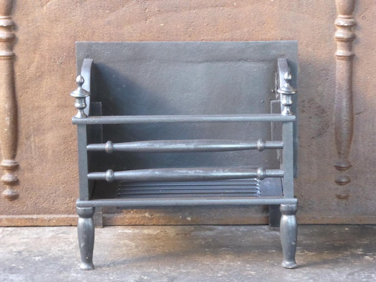 English Victorian style fireplace basket or fire basket. The fireplace grate is made of wrought iron and cast iron.