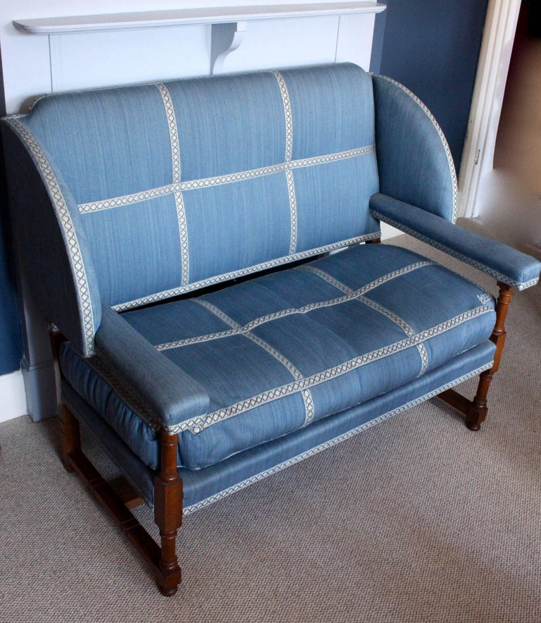 A beautifully elegant English walnut settee by Morant & Co. of New Bond Street, London, circa 1900-1910. Covered in an attractive blue linen with a contrasting cream and blue cross stitch design standing on block and baluster turned