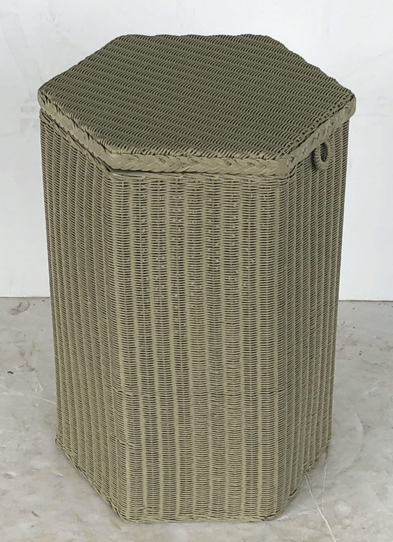 A fine Lloyd Loom hexagonal linen hamper or basket, synonymous with Classic English style, featuring a tall six-sided hamper with hinged lid of woven wicker and wire over a wood frame stretcher.  Perfect for an indoor or outdoor garden room, garden,