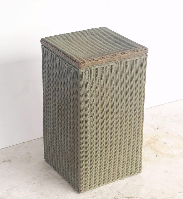 A fine Lloyd Loom square linen hamper, synonymous with classic English style, featuring a tall hamper with hinged lid of woven wicker and wire over a wood frame stretcher.  Perfect for an indoor or outdoor garden room, garden, or conservatory, this