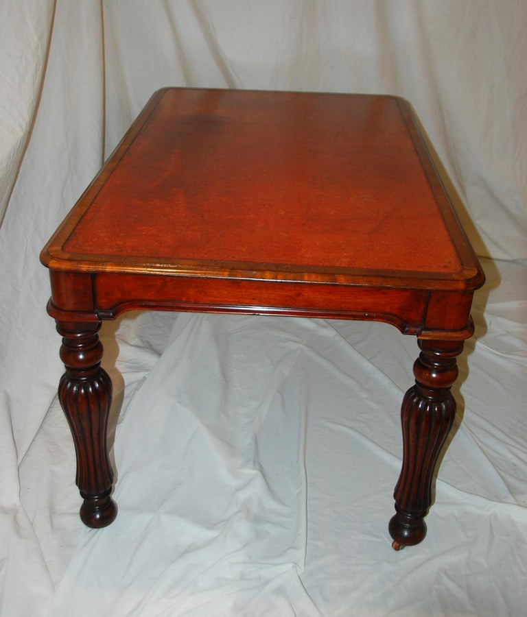 English William IV period mahogany writing table with inset gold tooled old leather writing surface, turned and reeded shaped legs, molded curved skirt to all sides. This medium sized writing table exudes the stylishness of William IV without being