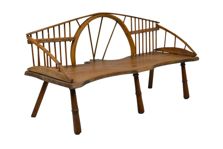 Quirky version of the Windsor style bench. A Windsor chair is a chair built with a solid wooden seat into which the chair-back and legs are round-tenoned, or pushed into drilled holes, in contrast to standard chairs, where the back legs and the