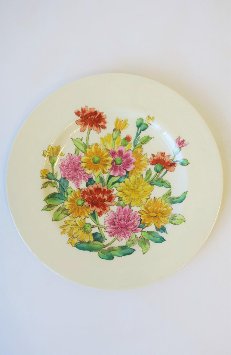 A beautiful English plate depicting Zinnia flowers, circa early-20th century, England. Flower colors include pink, red/orange, and yellow, with green leaves and vines. A beautiful plate for eating/entertaining or as wall art. Marked