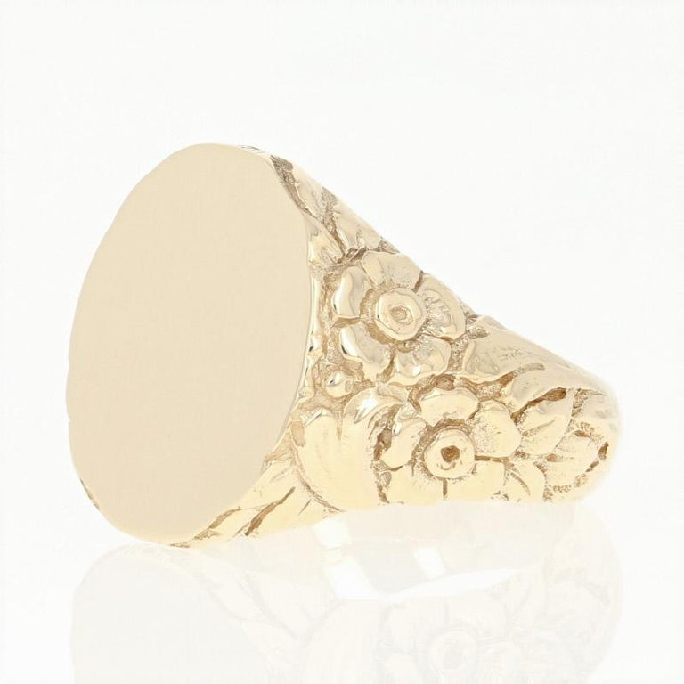 Elegantly crafted in 14k yellow gold, this antique signet ring showcases an oval-shaped face framed by tapered shoulders which display an ornately etched floral motif. This piece is engravable and can be personalized by your local jeweler.    This