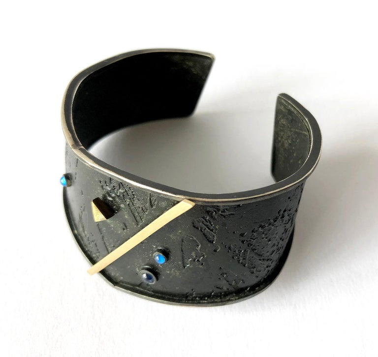 Post modernist cuff bracelet created by Enid Kaplan of New York City, circa 1984.  Bracelet is comprised of oxidized textured silver with floating blue sapphire cabochons and 18k gold geometric accents.  Signed Kaplan, 84 and in excellent vintage