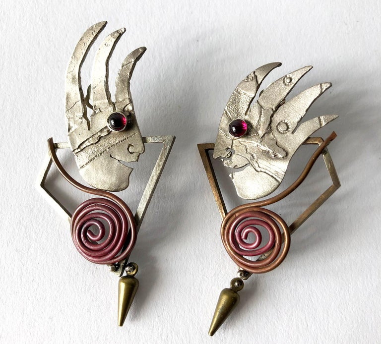 Pair of hand made sterling silver, 14k gold, brass, carnelian and onyx earrings created by New York jeweler and artist, Enid Kaplan.  Earrings are of the clip back variety and are signed Enid Kaplan, 1997.  In very good, unworn vintage condition.