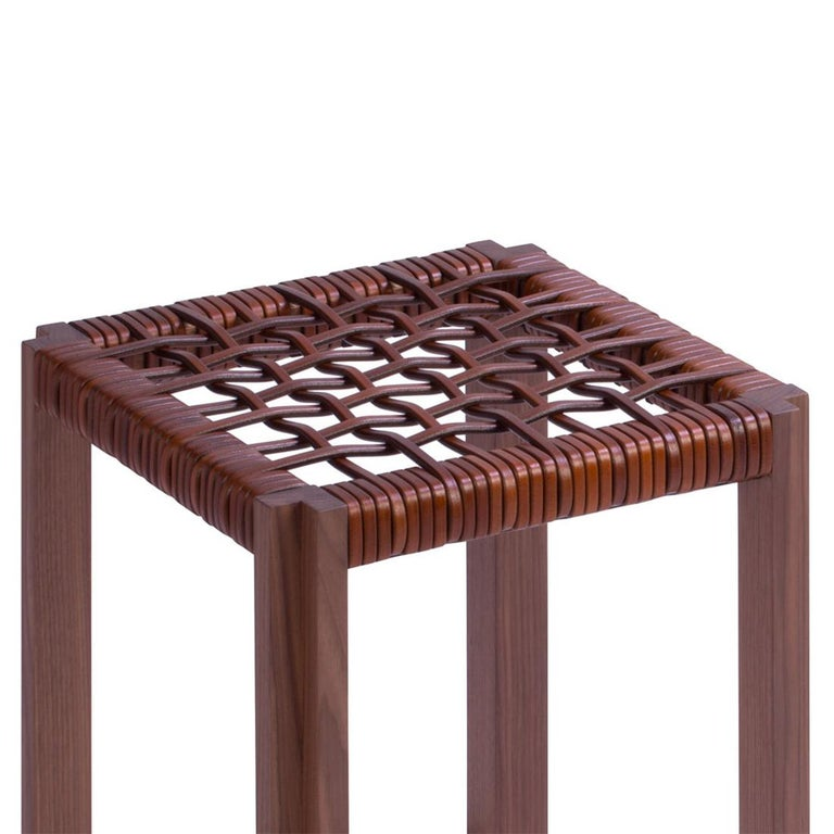 Stool enlaced leather with structure in solid walnut and seat made with enlaced genuine brown leather. Also available in solid walnut in wenge stained with enlaced genuine black leather.
