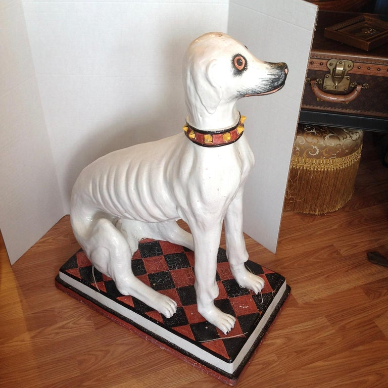 A substantial terra cotta rendering with a glazed finish. The dog is sitting on a