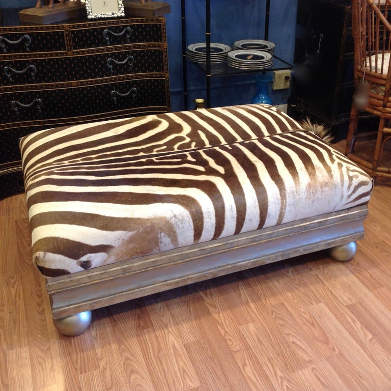 Fashioned from a complete hide sporting its mane.  The ottoman is cocktail table height and is supported by a silver gilt wood  trimmed base terminating in ball feet.