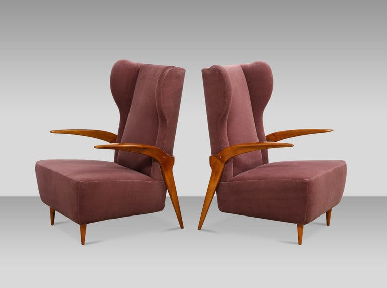 Pair of sculptural lounge chairs attributed to Enrico Ciuti. Elegant open armchairs of cherrywood, and upholstered seat with winged-backrest. Great details to overall form.
