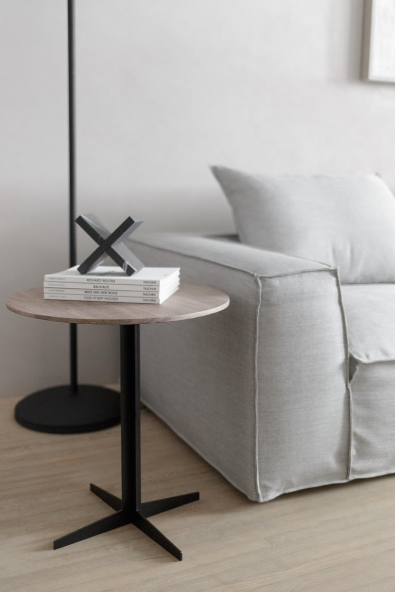 Side table with walnut veneer top on a laser-cut steel structure finished in matte black electrostatic paint.