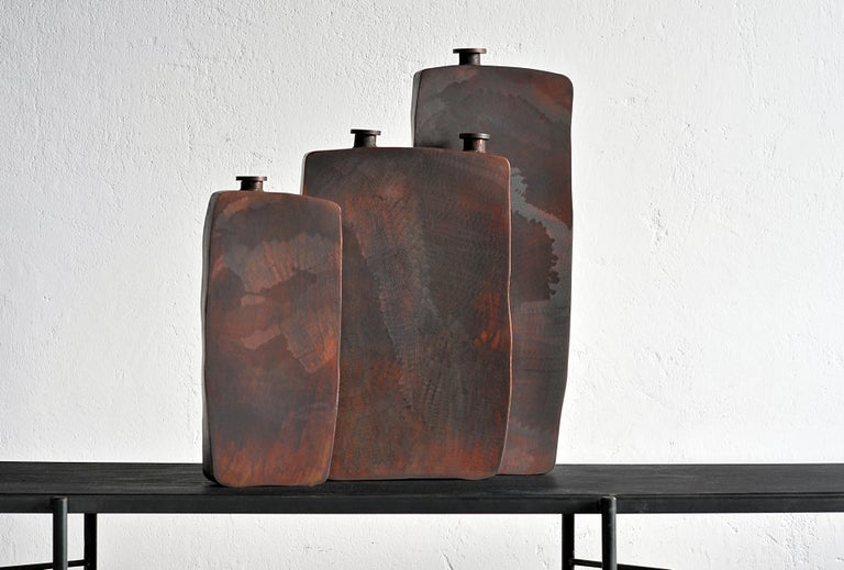 Ensemble of three brown bottles by Lukasz Friedrich Dimensions: Small bottle 15 x 5 x H 34 cm Medium bottle 24 x 5.5 x H 40 cm Large bottle 19.5 x 4.5 x H 50 cm Materials: Patinated steel.