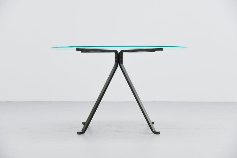 Very nice minimalistic dining table designed by Enzo Mari and manufactured by Driade, Italy, 1973. This table has heavy solid metal folded frame and a partially sanded round glass top which looks really nice. The tables is in very good original