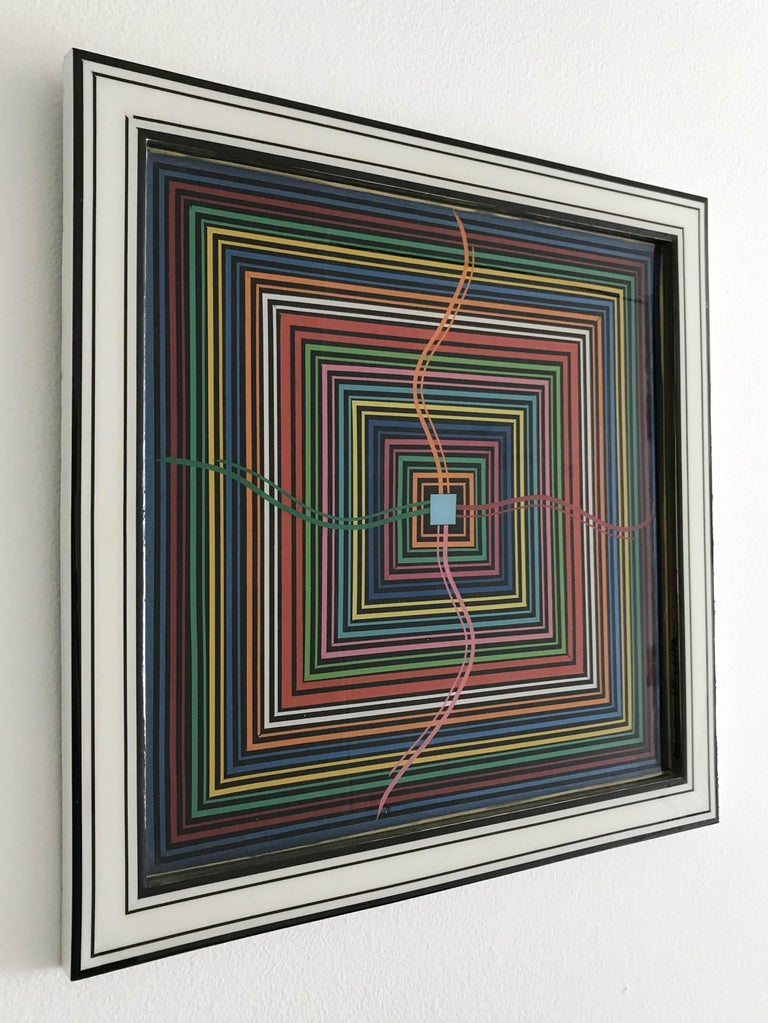 Epicenterby Mauro Oliveira, signed. Vinyl tapes, acrylic paint covered with resin on wood frame. A certificate of authenticity issued by the artist is included. Height: 18 inches / Width: 18 inches / Depth: 0.75 inches 1 in stock in Palm Springs