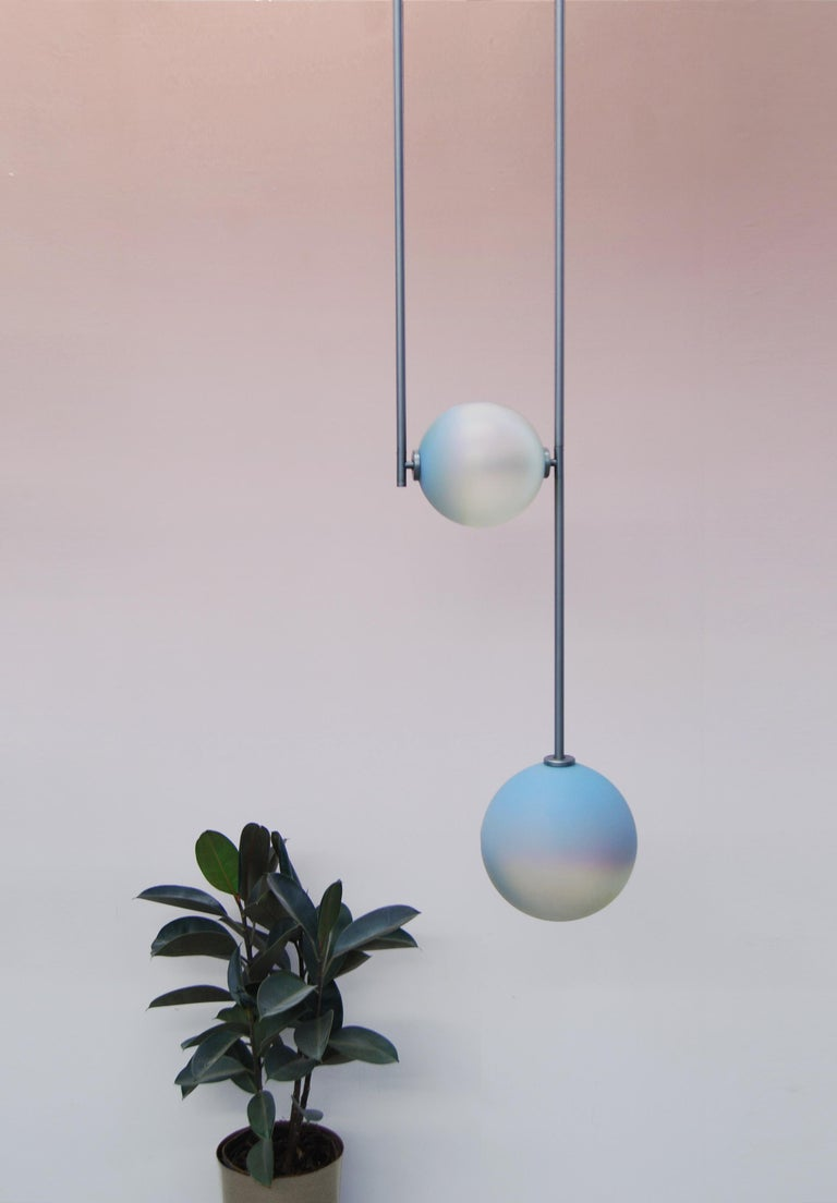"""Equalizer chameleon globe pendant light by Ladies & Gentlemen Studio  Dimensions: Height variable, 12"""" round canopy Materials: Copper, brass, wire, cord Finishes: Black anodize/bronze   Anodize/olive anodize  Glass: cream/smokey"""