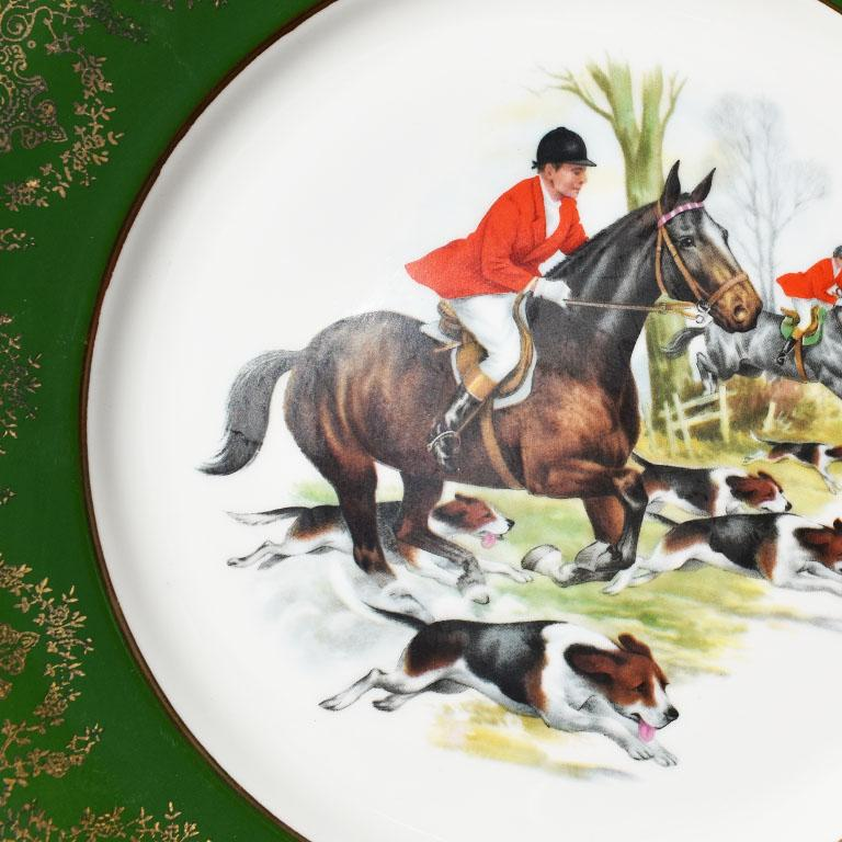 A green and gold ceramic plate of an equestrian hunting scene. This lovely piece features a thick green border with gold detail. The center of the plate depicts a team of hunters on horseback in red coats amidst hunting dogs.   Measures: 10.5