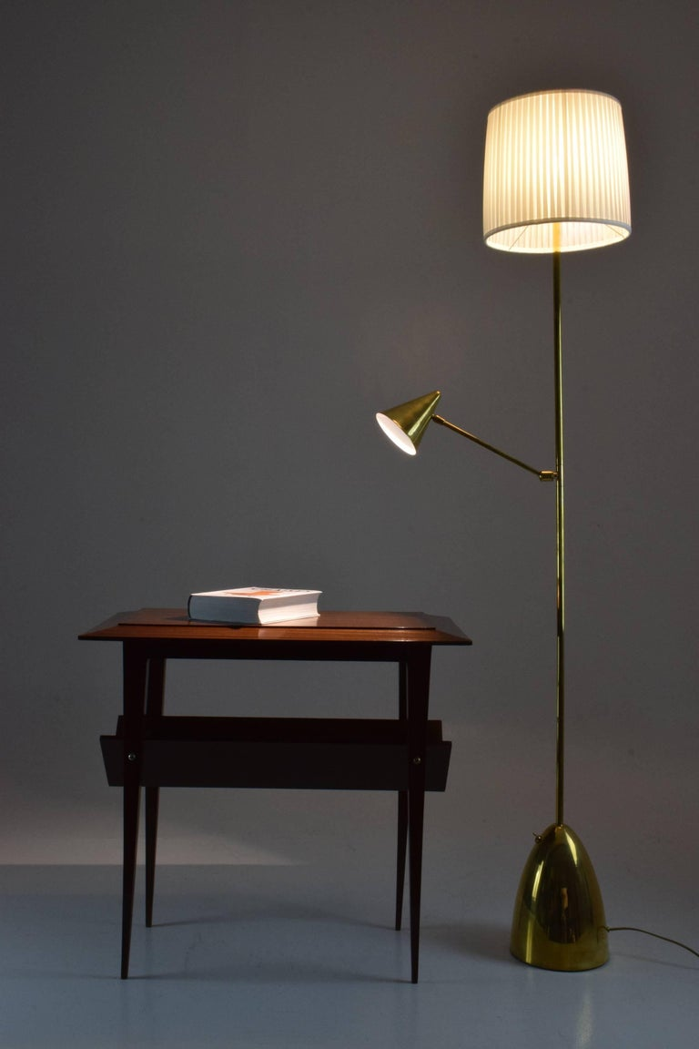 Contemporary handcrafted floor lamp composed of a gold solid polished brass structure and two shades. The second shade positioned mid-length articulates at the base and at the shade so you can orientate the reading light with ease. Both lighting