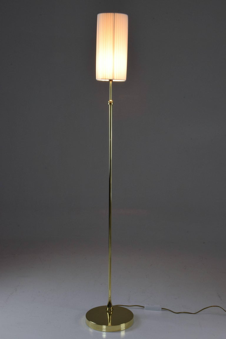 Contemporary handcrafted floor lamp composed of a solid brass structure -pictured here in a polished finish - which adjusts in height and is designed with a pleated white fabric lampshade.   Flow collection, Equilibrium-I model II 21st century