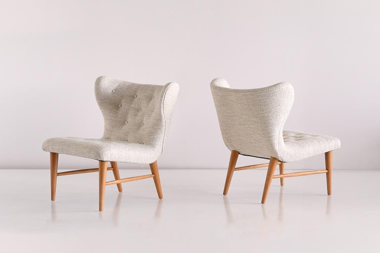 This rare pair of lounge chairs was designed by Eric Bertil Karlén and produced by his company Firma Rumsinteriör in Sweden in the 1940s. The elegant shape of the design is emphasized by the buttoned wing shaped back and seat. The beech wood frame