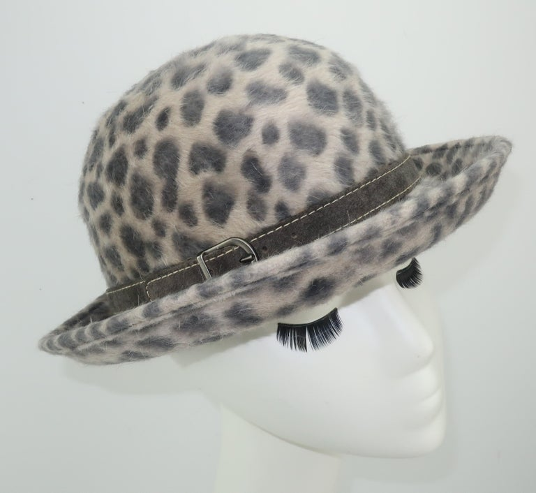 A bowler hat silhouette from Eric Javits with an animal print mohair in shades of gray with a suede buckled band.  Eric Javits toppers are known for their malleable construction and indeed this hat could be manipulated to create a down turned brim,