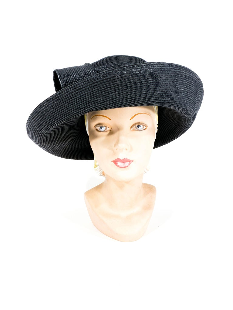 1980s to 1990s black coated straw woven hat with a tall crown, wide curled brim, and an oversized structured bow along the wide matching hatband.