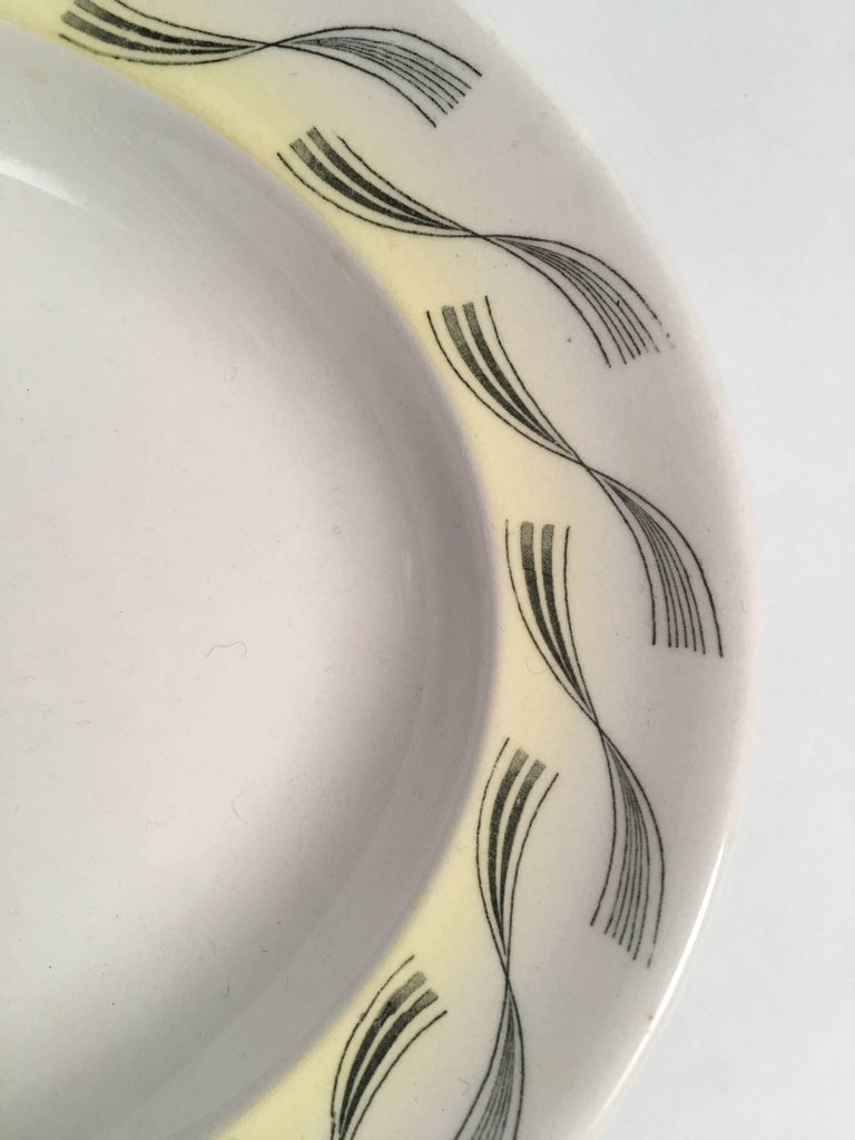 A rare Eric Ravilious designed oval platter for Wedgwood from the Garden Series, depicting a woman under a tree with umbrellas and a striped tent nearby, within a sunny landscape, in transfer printed black with yellow highlights on a white field.