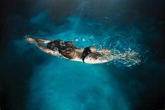 ILLUMINATION, hyper-realism, woman underwater, swimming, dark water, blue