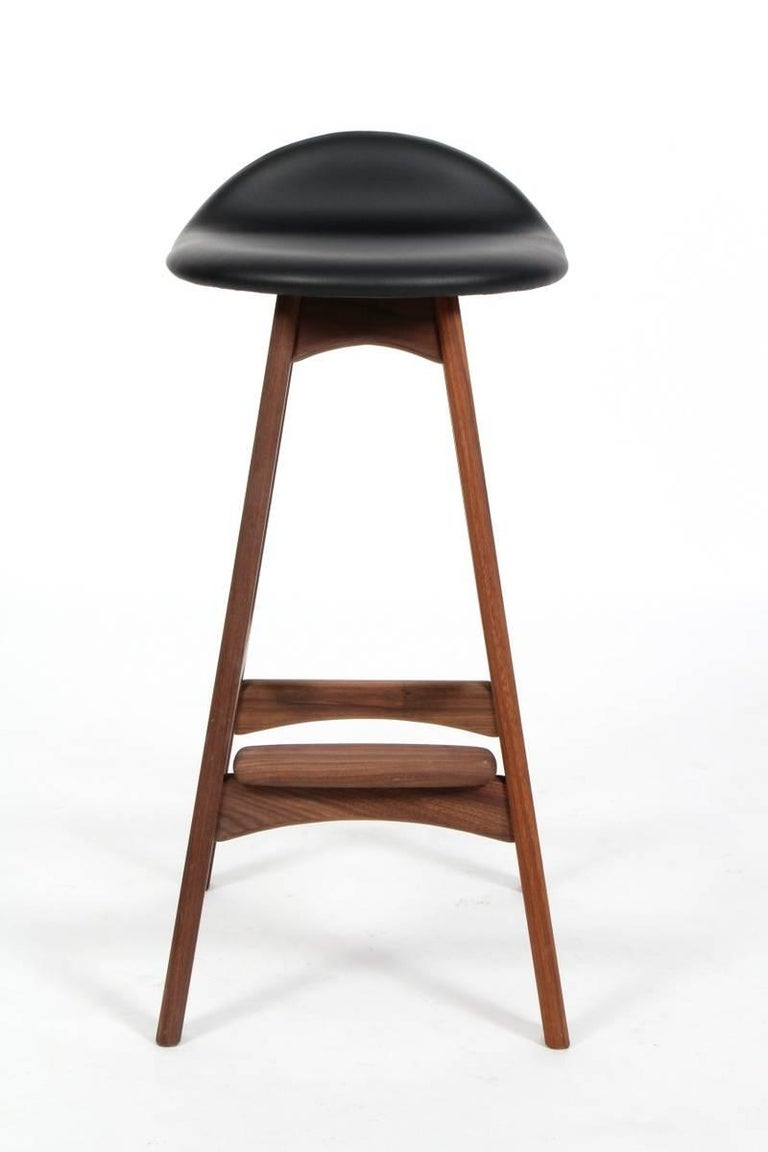 Sculpted stools of walnut wood, seats upholstered in black leather, model OD 61. Designed by Erik Buch in the 1960s for by O.D. Møbler in Denmark.