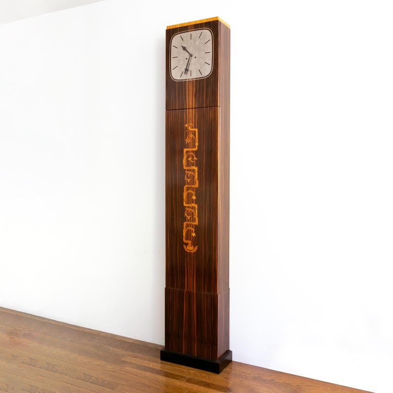 Erik Chambert, Swedish Art Deco floor clock in rosewood and decorative marquetry depicting stylized foliage. The clock's face is polished pewter with engraved imagery all of which refer to the passing of time, zodiac figures, stars, our sun & moon,