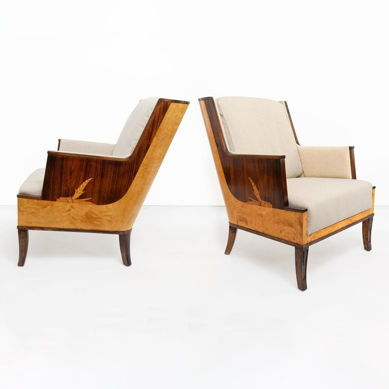 Elegant pair of Swedish art deco armchairs / lounge chairs designed by Erik Chambert. Chairs feature a sleek wood veneered frame in rosewood and birch veneer and a beautifully rendered marquetry design on each side. Angular arms create a modern