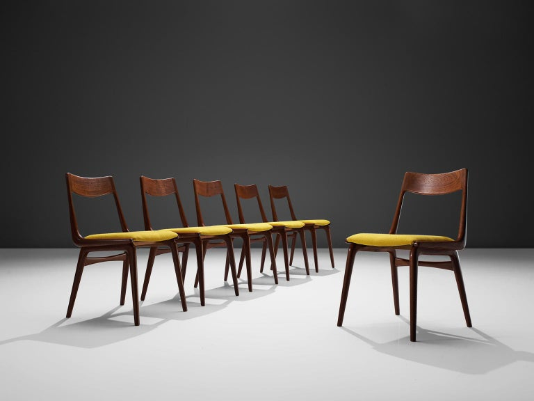 Erik Christiansen for Slagelse Mobelvaerk, 'Boomerang' chairs, teak and yellow fabric, Denmark, 1950s.  Clearly shaped chairs with elegant legs and back. On the sides of the seating there is a boomerang shaped wood construction that ends in the