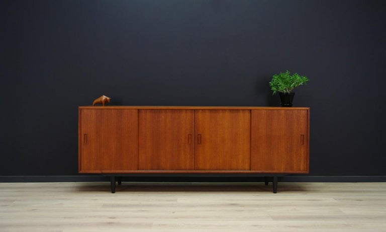 A stylish sideboard, Danish minimalism from the 1960s-1970s, a classic form with sliding doors designed by Erik Jensen, produced by Westergaard Møbelfabrik. Inside practical shelves. Sideboard veneered with teak. Preserved in good condition (small