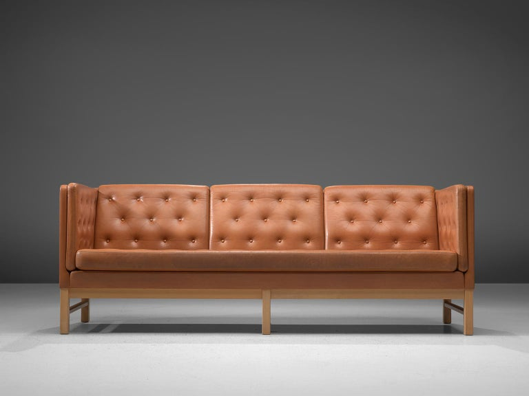 Erik Ole Jørgensen for Erik Jorgensen Møbelfabrik, sofa model EJ 315-3, wood and leather, Denmark, 1972.   Elegant three-seat sofa by Erik Ole Jørgensen. This sofa has a luxurious appearance due to the tufted cognac leather. The orderly placed