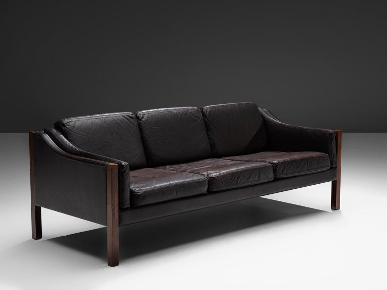 Erik Jørgensen, settee, in dark brown leather and rosewood, Denmark, 1963.  This sofa by Jørgensen features an elegant design. This sofa has a low, curved back, which smoothly runs over into the armrests with detailed piping. Seating and back