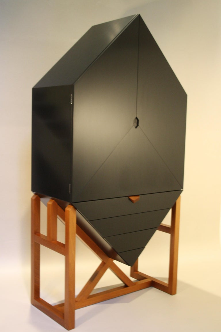A unique sculptural cabinet made by the Danish cabinet Maker Erik Jørgensen Møbelfabrik commissioned in 1982. The cabinet is made from black lacquered wood and is standing on a fruitwood base. It has four drawers and three doors, one of which