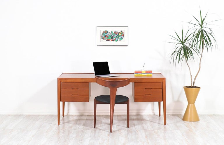 Danish Modern executive desk designed by Erik Riisager Hansen and manufactured by Haslev Møbelsnedkeri in Denmark, circa 1950s. This sleek design features a teak wood case with tall spindle legs and six front drawers creating an eye-catching profile