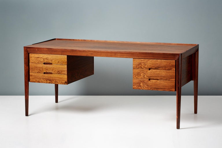 Erik Riisager Hansen writing desk, produced by Haslev Mobelsnedkeri in Haslev, Denmark, circa 1950s. The top is rosewood veneer with solid rosewood legs and mouldings. Each side has a 3-drawer carcass with pullout / pull-out trays.  Measures: H