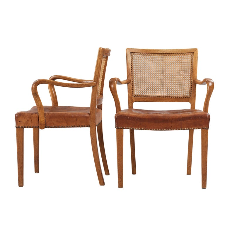 Set of 12 Erik Wørts dining chairs in solid oak, backrests in cane and seats in original Niger leather for cabinetmaker Henrik Wørts Møbelsnedkeri. The set consists of 10 side chairs and 2 armchairs. Designed 1945.  Litterature: 40 years of