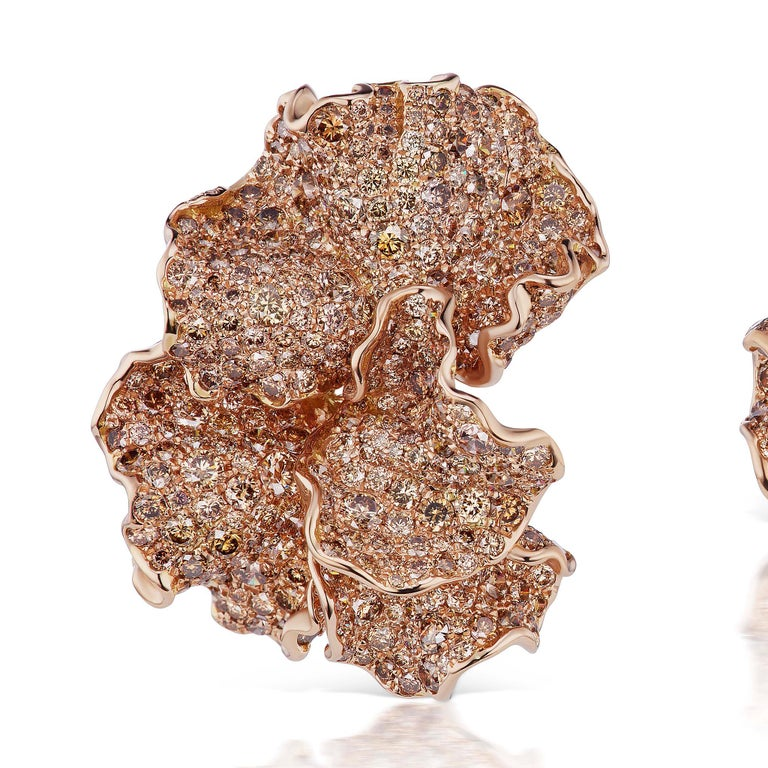 A pair of modern Erith earrings by Neha Dani. The asymmetrical earrings, executed in 18 karat rose gold, are comprised of three delicate, highly textured petals, each studded in graduating hues of 765 mixed-cut cognac, amber, dark honey and white