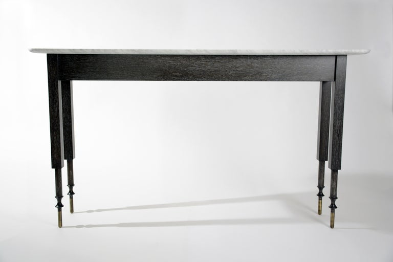 """Erland console table • Size: 60"""" W x 16"""" D x 33"""" H • Wood finish: Charcoal cerused white oak • Stone top: White Carrara marble (honed and sealed) • Accent metal (feet/sabots): Antique brass (AB) finish  This is an excellent condition showroom"""