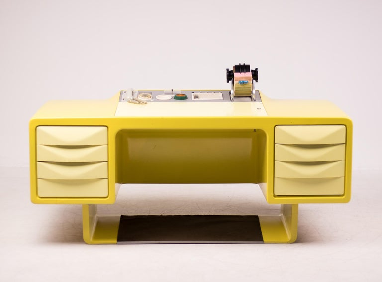 This exceptionalWilhelm Werndl desk is made of molded fiberglass with brushed stainless steel control panel.  The control panel holds an original built in phone, working clock, porcelain inset trays and holders and a Rolodex.  Writing surface