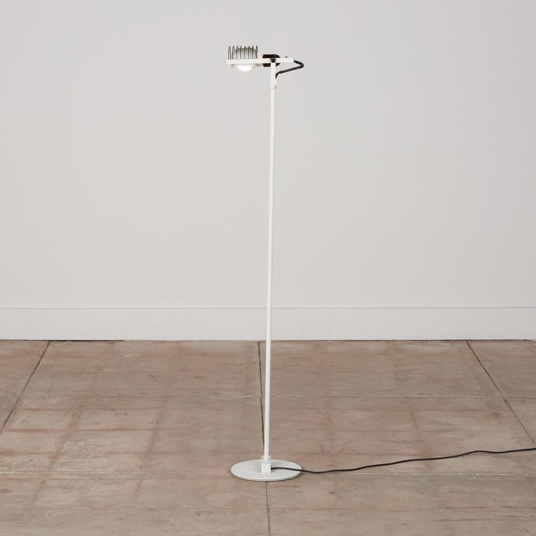 """Ernesto Gismondi """"Sintesi"""" floor lamp for Artemide, Italy, c. 1970s. The lamp features a white lacquered metal base and stem with black metal cage detail surrounding the housing for the bulb. The head of the lamp is adjustable and it features the"""